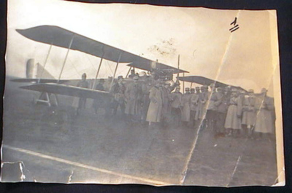 Snapshot of an Early Twentieth-Century Biplane with Military Personnel. Aviation.