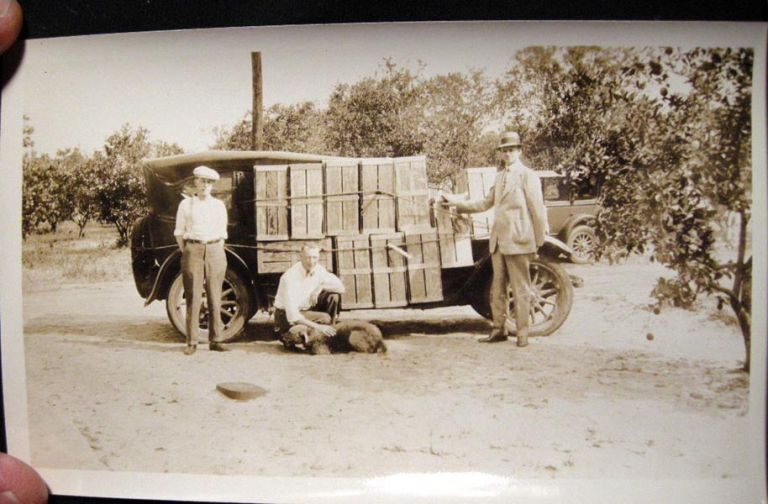 1929 Snapshot Photograph of a group of men in a Florida Orange Grove, with their vehicle loaded down with crates of Oranges. Photography.