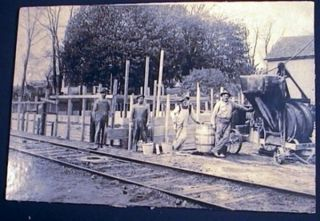C. 1920 photograph of Crew of Men in Concrete Foundation Crew, with Equipment Near a Railway....